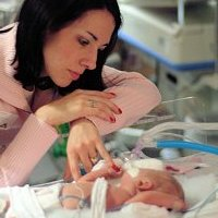 Mother looking at premature baby in the NICU